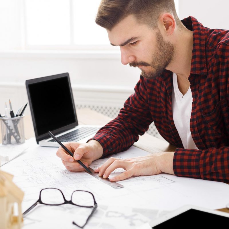 young-architect-working-with-blueprints-in-the-off-4S9JQT5.jpg